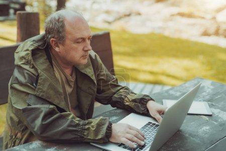 Photo pour Un vieil homme forestier sérieux dans une salopette vert foncé avec la tache chauve et un cheveu gris est assis à la table sur un banc en bois à l'extérieur et en utilisant son ordinateur portable avec une tablette numérique à côté de lui - image libre de droit