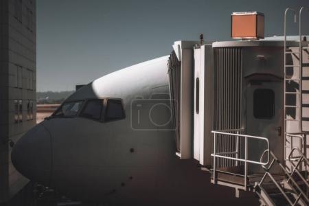 Photo pour Vue rapprochée du nez de l'avion lors d'un embarquement ou d'un entretien dans une aire de départ d'un aérogare moderne avec une échelle coulissante garée à la porte d'une entrée en classe affaires - image libre de droit