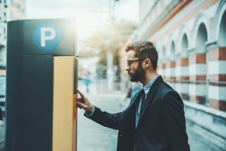 Photo pour Homme sérieux barbu entrepreneur dans les lunettes et un costume formel utilise terminal de la station de paiement de stationnement ; bel homme d'affaires dans les lunettes et avec la barbe payer son temps de stationnement via kiosque automatique - image libre de droit