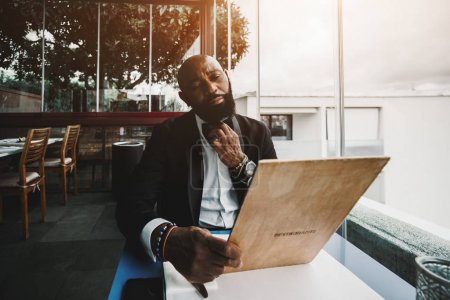 Photo for An elegant bald bearded mature African man in a formal suit is straightening a collar while sitting next to the window indoors of a luxurious restaurant and reading a menu to choose a dish or a drink - Royalty Free Image