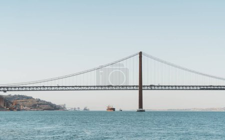 Photo pour Une vue de l'eau d'un énorme pont «Ponte 25 de Abril» suspendu, sur le Tage à Lisbonne, au Portugal un jour chaud matin avec l'horizon à l'arrière-plan - image libre de droit