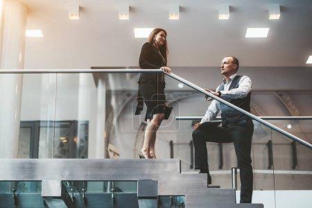 Photo pour Deux associés discutent dans l'escalier du bureau : un bel homme entrepreneur avec un ordinateur portable à la main et sa collègue - une femme d'affaires caucasienne avec la tablette numérique - image libre de droit