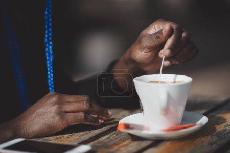 Photo pour Vue rapprochée des mains d'une jeune femme noire brassant du sucre dans une tasse de café avec une cuillère dans un café extérieur avec un smartphone sur une table en bois à côté d'une soucoupe en céramique blanche ; foyer sélectif - image libre de droit