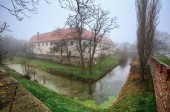 The moated manor house in the market town of Guntersdorf on a foggy winter day. Lower Austria.