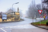Vehicles moving on a winding country road through historical town on a foggy winter day. Guntersdorf, Lower Austria.