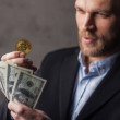 Man holding money and bitcoin. Focus on coin...