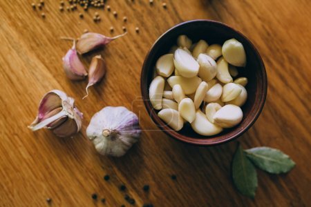 Photo for Ceramic Bowl of garlic on wooden table - Royalty Free Image