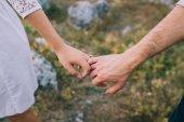 Pár se drží navzájem ruce