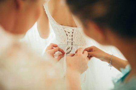 bridesmaids helping lacing up dress
