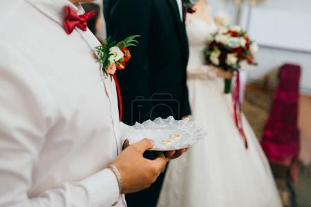 Man holding wedding rings in church
