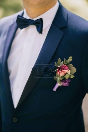 groom in a blue suit in  boutonniere