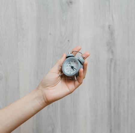 girl holding small clock