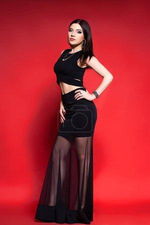 Foto de Sexy morena posando en negro sobre fondo rojo . - Imagen libre de derechos