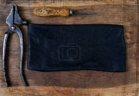 Leather craft tools on a wooden background. Craftmans work desk.