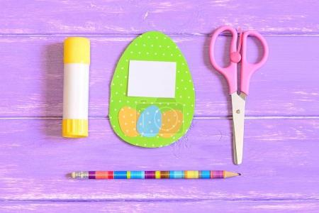 How to make Easter egg greeting card. Step. Instruction. Colored cardboard greeting card with eggs, scissors, glue stick, pencil on a wooden table. Children Easter paper gift idea. Top view. Closeup