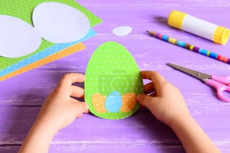 Small child holds a Easter paper card in hands. Child made Easter greeting card in egg shape. Materials for art activity on a wooden table. Paper crafts concept in kindergarten or at home