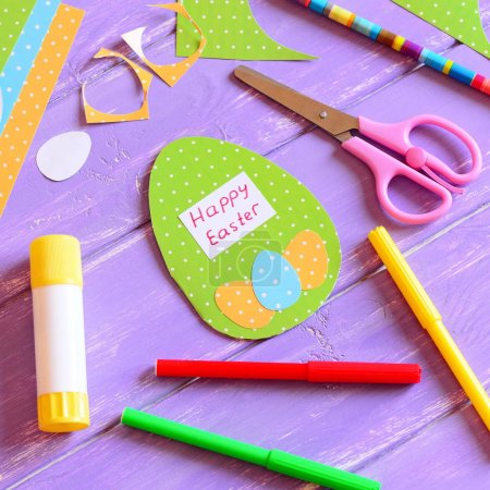 Happy Easter card in egg shape. Materials and tools to create Easter paper greeting card. Easy and fun Easter paper crafts for kids