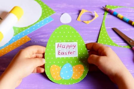 Little child holds a Easter paper card in hands. Child shows Easter greeting card in egg shape. Materials for kids activity on a wooden table. Quick and easy Easter paper crafts for kids
