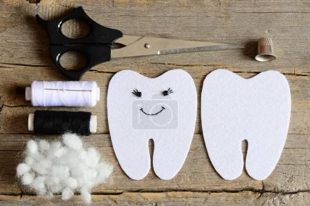 Making a felt tooth fairy. Step. Guide. On one side embroidered with black thread and beads eyes and mouth. Crafts supplies on vintage wooden table. Easy sewing diy for kids. Top view. Closeup