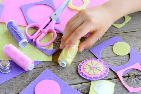 Teaching children to sew by hand concept. Small child made a flower from felt circles. Child takes thread in hand. Beaded felt flower crafts, craft supplies on wooden table. Easy and quick applique