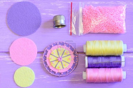 Felt flower, colored felt circles, thread spools, needle, thimble, pink beads on a wooden table. Sewing felt flower tutorial. Simple round felt flower crafts for kids. Top view
