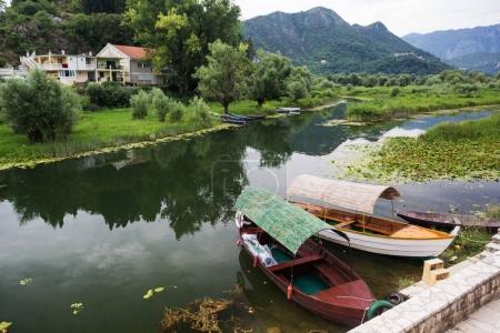 Two boats at the pier on the river bank. Mountains and bushes in