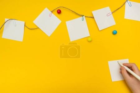 Child writes a note on a yellow background. The paper notes.