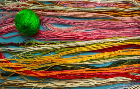 Bright Green clew on a background of colorful threads