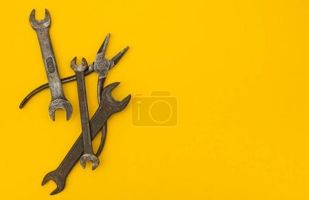 Pliers and wrenches on a yellow background, with space for text.