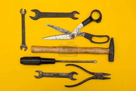 Set of old rusty tools on a yellow background, with space for te
