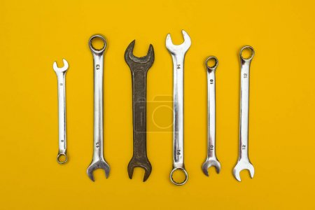 Old wrench on a background of new. yellow background