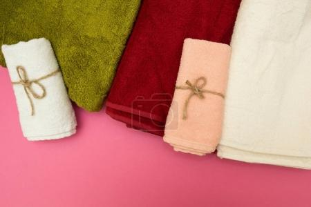 Multi-colored towels on a pink background