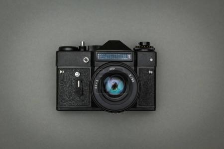 Black retro camera on a gray background.