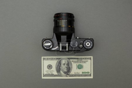 Black retro camera and one hundred dollars on a gray background