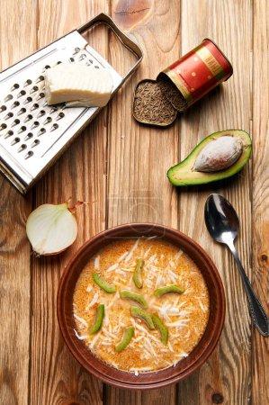 Photo pour Le chef a récemment terminé de cuisiner une délicieuse soupe pour le dîner dans la cuisine. Cuisine à l'ancienne. Sur la table, une assiette de fromage, soupe de pommes de terre, avocat, oignon, râpe, cumin, épices . - image libre de droit