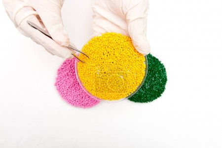 Plastic pellets . Colorant for polymers in granules. Plastic pellets in the hands with gloves and tweezers
