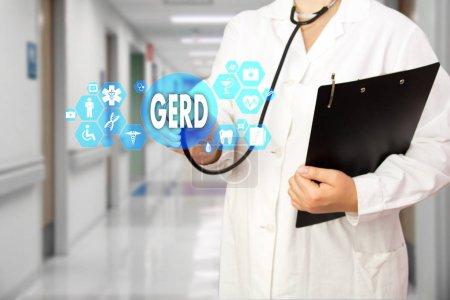 Photo pour Médecin avec stéthoscope et mot GERD, reflux gastro-œsophagien en connexion réseau médical sur l'écran virtuel sur fond hospitalier.Concept de technologie et de médecine . - image libre de droit