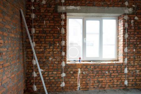 Photo pour Maison de construction. Effectué des travaux sur le câblage électrique et l'installation de windows, préparé la surface des murs en briques de plâtre - image libre de droit