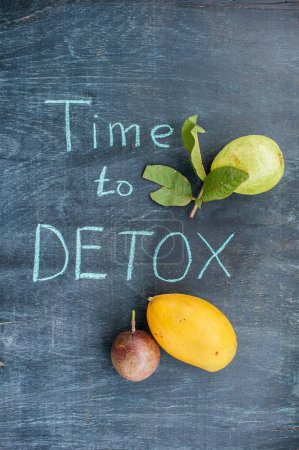 TIME TO DETOX chalk inscription on the wooden table fruits: mango, passion fruit and guava. Health Concept