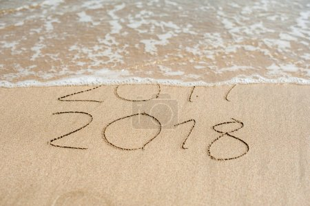 Photo for New Year 2018 is coming concept - inscription 2017 and 2018 on a beach sand, the wave is almost covering the digits 2017. - Royalty Free Image