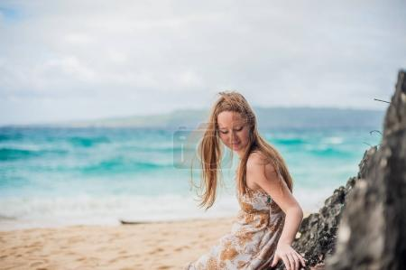 Photo for A girl sits on a rock on the beach of Boracay Island - Royalty Free Image