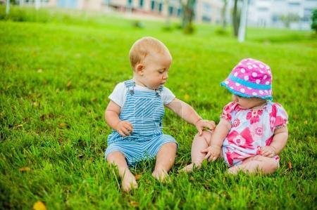 Photo pour Deux heureux bébé garçon et une fille age de 9 mois-vieux, assis sur l'herbe et interagissent, parlent, regardent les uns les autres. Enfants sont reposent sur une chaude journée d'été sur l'herbe. - image libre de droit