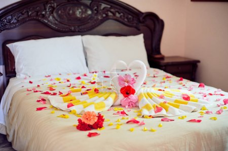 White two towel swans and red rose on the bed in Honey moon suit
