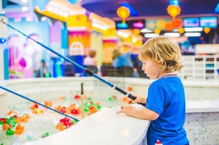 Cute boy in the playroom fishing.