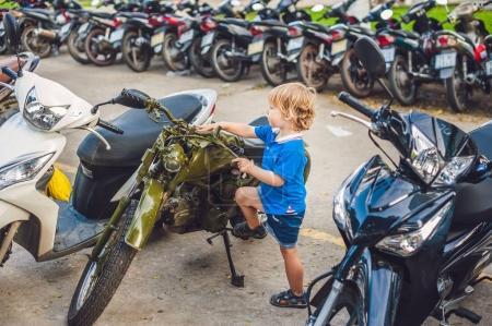 Photo pour Garçon blond mignon regardant la nouvelle moto de moto vintage eatables. - image libre de droit