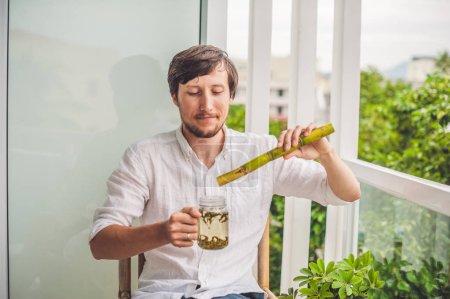 Photo pour Concept de sucre de canne. L'homme qui mange de la canne à sucre et boit du thé . - image libre de droit