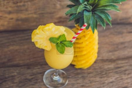 Photo for Pineapple and pineapple smoothie against the background of a branch of a palm tree. - Royalty Free Image