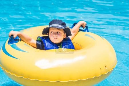 boy is riding on an inflatable donut