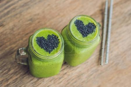 Photo for Fresh green smoothies with banana and spinach with heart of sesame seeds. Love for a healthy raw food concept. - Royalty Free Image