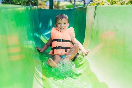 boy in a life jacket slides down
